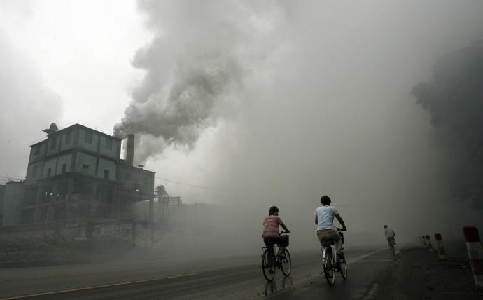 Cyclists pass through thick pollution fr