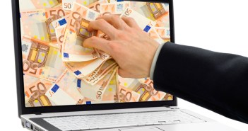 Conceptual shot of businessman's hand taking out euro banknotes out of a laptop display