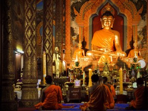 Monks pray before a statue of the Buddha at evening prayers