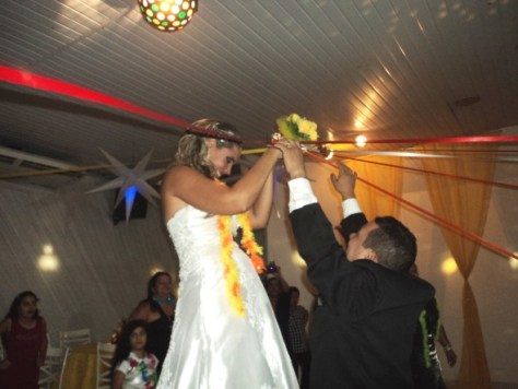 Momento de descontração da noiva cortando fitas coloridas para entrega do seu buquê