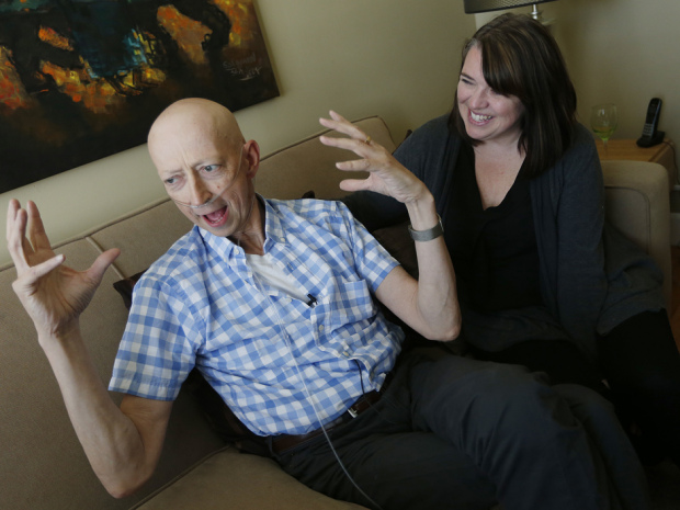***FREELANCE PHOTO - POSTMEDIA NETWORK USE ONLY*** WINNIPEG, MANITOBA: APRIL 28, 2015 -- Mike O'Brien, who is dying of cancer, is photographed with his wife Robin as he tells a story about his young son Will in their Winnipeg home Tuesday, April 28, 2015.  In his life, on Facebook, and on his blog The Big Diseasy, Mike is approaching his death in a way that is funny, honest and unsentimental, and doesn't stick to the script we've come to expect from the terminally ill. Photo by John Woods for National Post (For National Post story by Jana Pruden Section Name: National; TRAX: )  // pruden-o'brien  // 0509 na die laughing