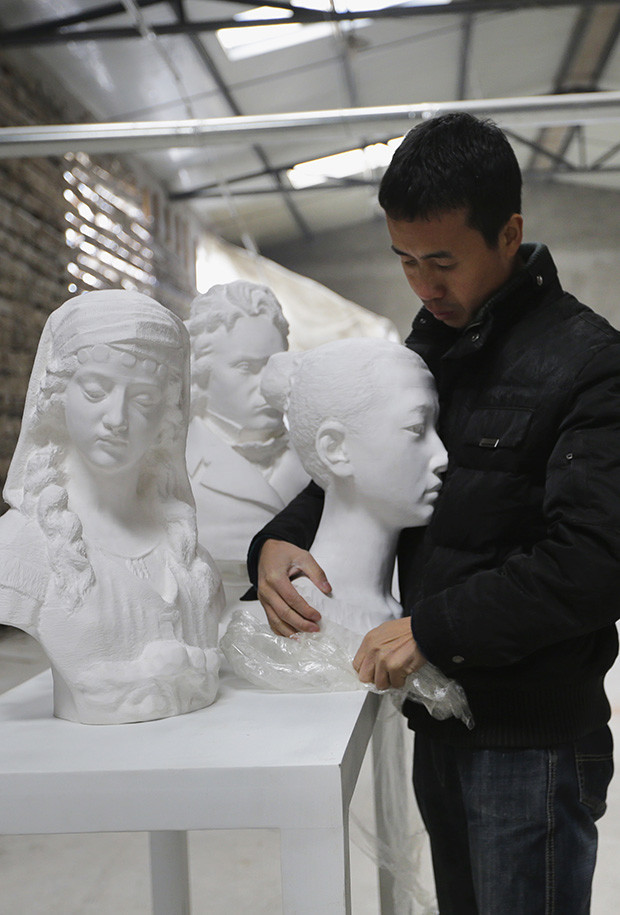 Chinese artist Li holds one of his paper sculptures at his studio on the outskirts of Beijing