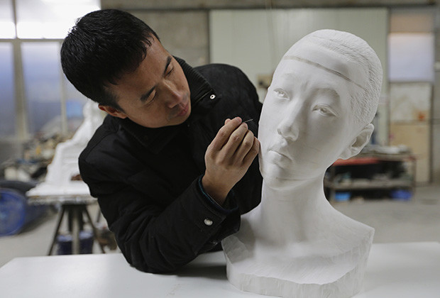 Chinese artist Li Hongbo uses an iron needle to remove dust from a paper sculpture work on the outskirts of Beijing