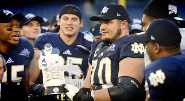 Notre Dame offensive tackle Zack Martin (70) is awarded the game's MVP trophy against the Rutgers Scarlet Knights in the Pinstripe Bowl at Yankees Stadium. Notre Dame won the game 29-16. Mandatory Credit: Joe Camporeale-USA TODAY Sports