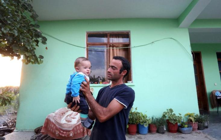 Lorenc Toska, 25, holds his baby son Ardit in the village of Suk, near the Albanian city of Fier, on June 29, 2015 (AFP Photo/Gent Shkullaku)