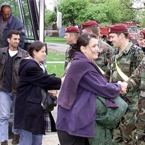 XVIII Airborne Corps soldiers from Fort Bragg, N.C., welcome Kosovo Albanians arriving at the reception center at Fort Dix, N.J. DoD Photo