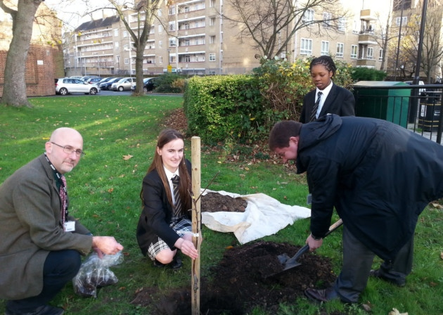 A model student who recently came from Albania, gives trees to Holloway School in London