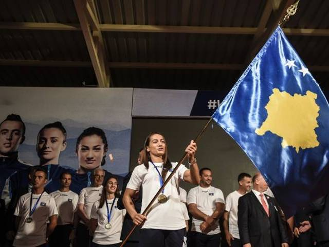 Kosovar judoka Majlinda Kelmendi (C) waves Kosovo's national flag during the flag handover ceremony in Pristina on July 29, 2016. PHOTO: AFP
