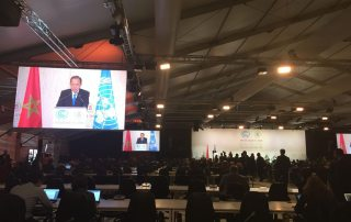 Secretary-General Ban Ki-moon (on screens) addresses a high-level event on accelerating climate action in Marrakech. Photo: UN News Centre