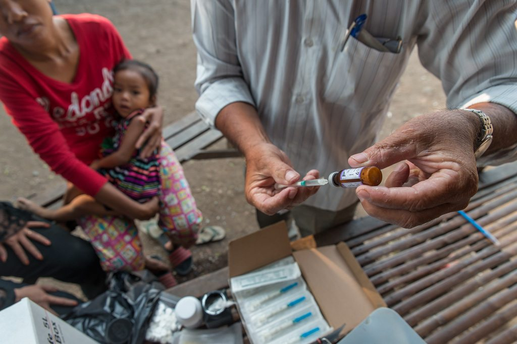 A health worker prepares to administer a vaccine to a child at a mobile vaccination unit, in Svay Pak village, an urban poor community in Rossey Keo district, Phnom Penh, Cambodia. Photo: UNICEF/Llaurado