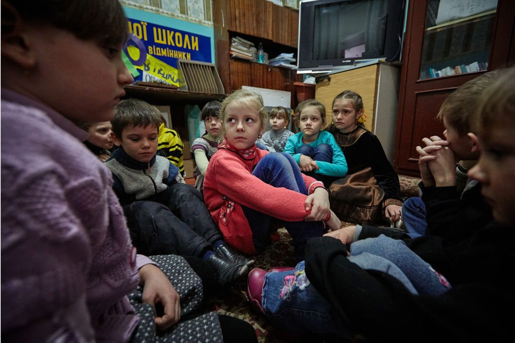 first-grade students in eastern Ukraine, including 6-year-old Sasha (in red sweater), participate in a drill to practice their response to a shelling. Photo: © UNICEF/UN053119/Zmey