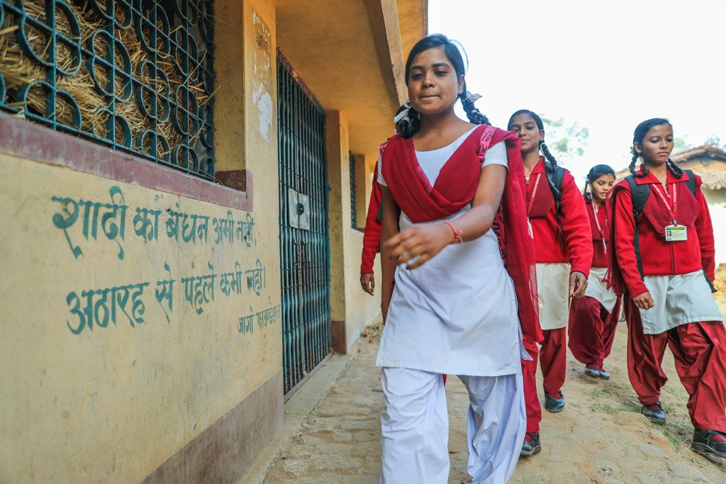 "A 16-year-old girl advocate against child marriage walks to her school, passing a sign that reads ""Now is not the time to get married, never marry before the age of 18,"" in her village in Giridih, Jharkhand state, India. Photo: UNICEF/Prashanth Vishwanathan"
