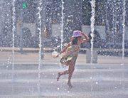 A girl enjoying water fountains amid city summer heat. Photo: WMO