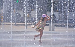 A girl enjoying water fountains amid city summer heat. Photo: WMO
