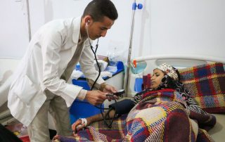 At the Al Sab'een Hospital in Sana'a, Yemen, a doctor checks on a girl suffering from cholera. Photo: UNICEF/UN066510/Fuad