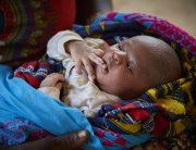 A nine-day-old baby boy is cradled by his mother (partially visible) in Bambaya Village in Fiama Chiefdom, Kono District, Sierra Leone. Photo: UNICEF/Phelps