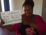 """A young woman holds a sign that says, """"In Zimbabwe, youth policy is not being implemented"""""""