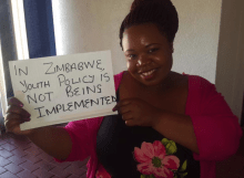 "A young woman holds a sign that says, ""In Zimbabwe, youth policy is not being implemented"""
