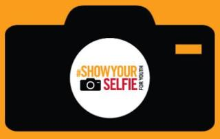 "The ""#ShowYourSelfie"" campaign logo, which features the outline of a black camera on an orange background"