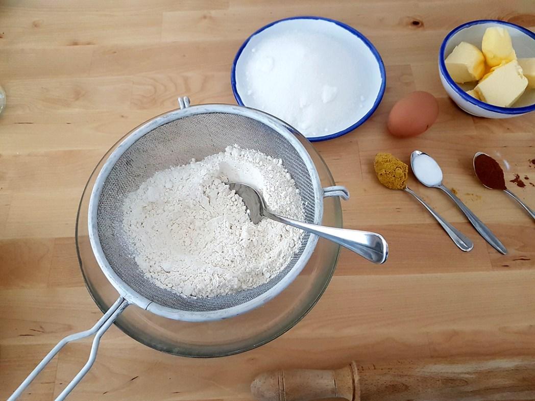 Galletas de jengibre tamizando harina