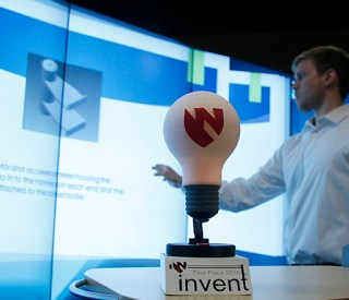 In the foreground is the 2016 Invent-a-Thon trophy, a 3D-printed model of a light bulb that is lit with LEDs. In the background, an officer of UNMC's 3D Maker's Club, Will Payne, prepares one of the competitors' presentations on the iEXCEL center's MultiTaction Wall.
