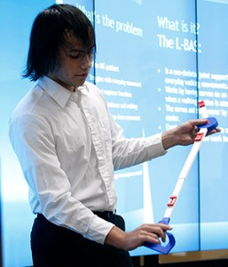 Millard South junior Harrison Pruitt demonstrates the winning design of the 2016 3D Invent-a-Thon to a panel of judges and about 28 onlookers Friday evening at UNMC's Sorrell Center.