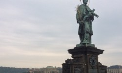 A photo of the statue of St John of Nepomuk with the river Vltava behind him - Prague, Czech Republic