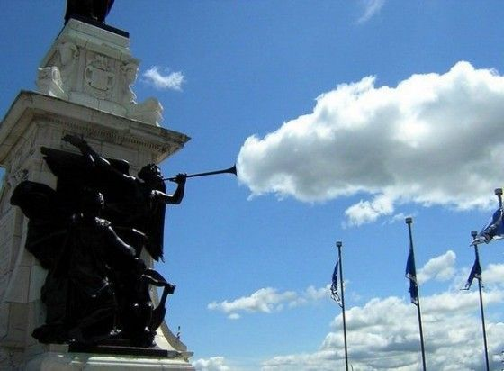 Statue blowing clouds away through trumpet