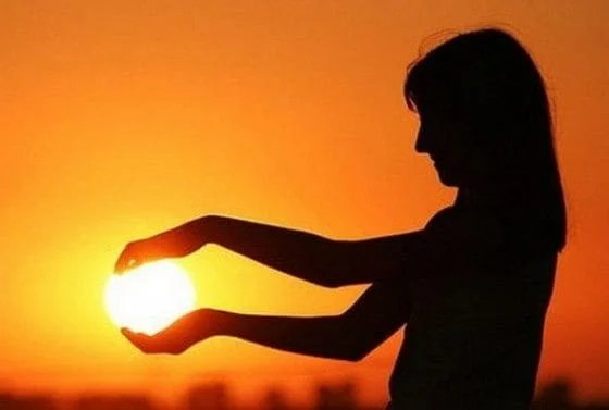 Woman holds a sun in her hands
