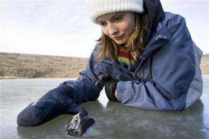 University of Calgary graduate student Ellen Milley poses with a fragment of a meteorite in a small pond. AP Photo/The Canadian Press, Geoff Howe