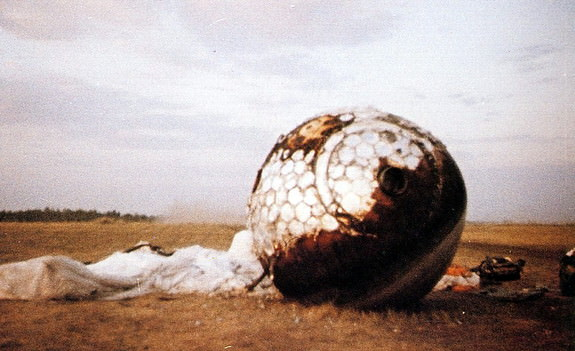 Here the re-entry capsule of the Vostok 3KA-3 (also known as Vostok 1) spacecraft (Vostok 1) is seen with charring and its parachute on the ground after landing south west of Engels, in the Saratov region of southern Russia. Credit: space.com