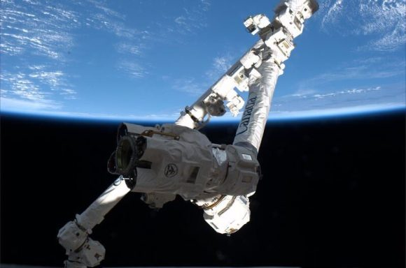Canadarm pictured through a winow aboard the ISS will be used to grapple the SpaceX Dragon after planned March 1 liftoff.  Credit: NASA/Thomas Mashburn