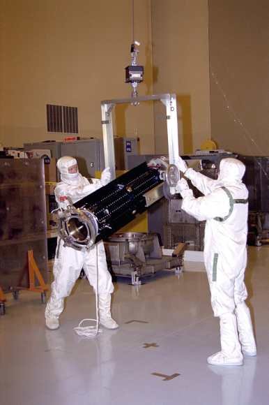 Technicians handle an RTG at the Payload Hazardous Servicing Facility at the Kennedy Space Center for the Cassini spacecraft. (Credit: NASA).