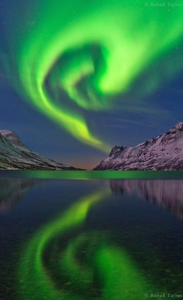 The northern lights or aurora borealis swirls over a fjord in the Norwegian Sea near Tromso, northern Norway. A mix of moonlight, aurora, and a nearby village illuminate the landscape. The Pleiades Star Cluster (the Seven Sisters) appears on the upper left. Credit and copyright: Babak A. Tafreshi.