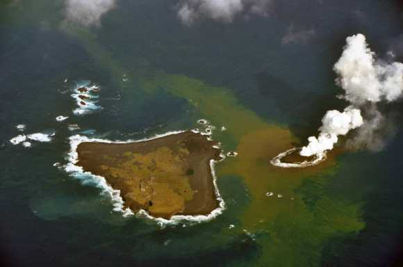An erupting undersea volcano forms a new island, shown by its nearest neighbor, Nishinoshima, a small unihabited island i