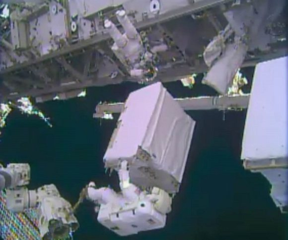 NASA astronaut Mike Hopkins holds a spare ammonia pump module during a spacewalk Dec. 24, 2013. Hopkins and fellow Expedition 38 Rick Mastracchio (top) performed two spacewalks to replace a pump blamed for crippling one of the International Space Station's two cooling loops Dec. 11. Credit: NASA TV (screenshot)