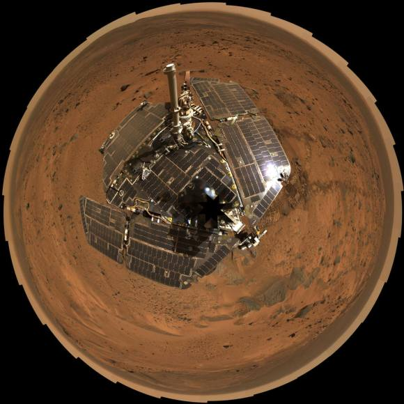 """This bird's-eye view from August 2005 combines a self-portrait of the spacecraft deck and a panoramic mosaic of the Martian surface as viewed by NASA's Mars Exploration Rover Spirit. The rover's solar panels are still gleaming in the sunlight, having acquired only a thin veneer of dust two years after the rover landed and commenced exploring the red planet. Spirit captured this 360-degree panorama on the summit of """"Husband Hill"""" inside Mars' Gusev Crater. During the period from Spirit's Martian days, or sols, 583 to 586 (Aug. 24 to 27, 2005), the rover's panoramic camera acquired the hundreds of individual frames for this largest panorama ever photographed by Spirit. Credit: NASA/JPL-Caltech/Cornell"""