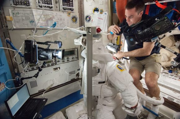 NASA astronaut Chris Cassidy examines a spacesuit during Expedition 36 in August 2013. Credit: NASA
