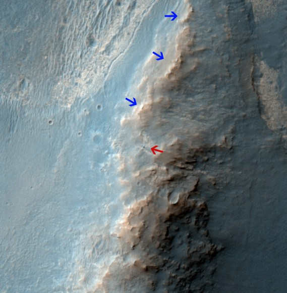"Opportunity Rover on 'Murray Ridge' Seen From Orbit .  The telescopic High Resolution Imaging Science Experiment (HiRISE) camera on NASA's Mars Reconnaissance Orbiter caught this view of NASA's Mars Exploration Rover Opportunity on Feb. 14, 2014.   The red arrow points to Opportunity at the center of the image. Blue arrows point to tracks left by the rover since it entered the area seen here, in October 2013.  The scene covers a patch of ground about one-quarter mile (about 400 meters) wide.  North is toward the top.  The location is the ""Murray Ridge"" section of the western rim of Endeavour Crater. Credit: NASA/JPL-Caltech/Univ. of Arizona"