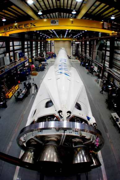 The Falcon 9 rocket with landing legs in SpaceX's hangar at