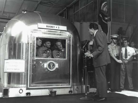 "President Nixon Greets the Returning Apollo 11 Astronauts. The Apollo 11 astronauts, left to right, Commander Neil A. Armstrong, Command Module Pilot Michael Collins and Lunar Module Pilot Edwin E. ""Buzz"" Aldrin Jr., inside the Mobile Quarantine Facility aboard the USS Hornet, listen to President Richard M. Nixon on July 24, 1969 as he welcomes them back to Earth and congratulates them on the successful mission. The astronauts had splashed down in the Pacific Ocean at 12:50 p.m. EDT about 900 miles southwest of Hawaii.  Credit: NASA"