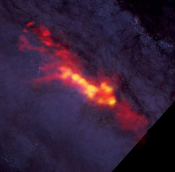 ALMA image of Sculptor (NGC 253), a 'starburst' galaxy with a diffuse envelope of carbon monoxide gas (in red) which surrounds star-forming regions (in yellow). The ALMA data are superimposed on a Hubble image that covers part of the same region. Credit: B. Saxton (NRAO/AUI/NSF); ALMA (NRAO/ESO/NAOJ); A. Leroy; STScI/NASA, ST-ECF/ESA, CADC/NRC/CSA