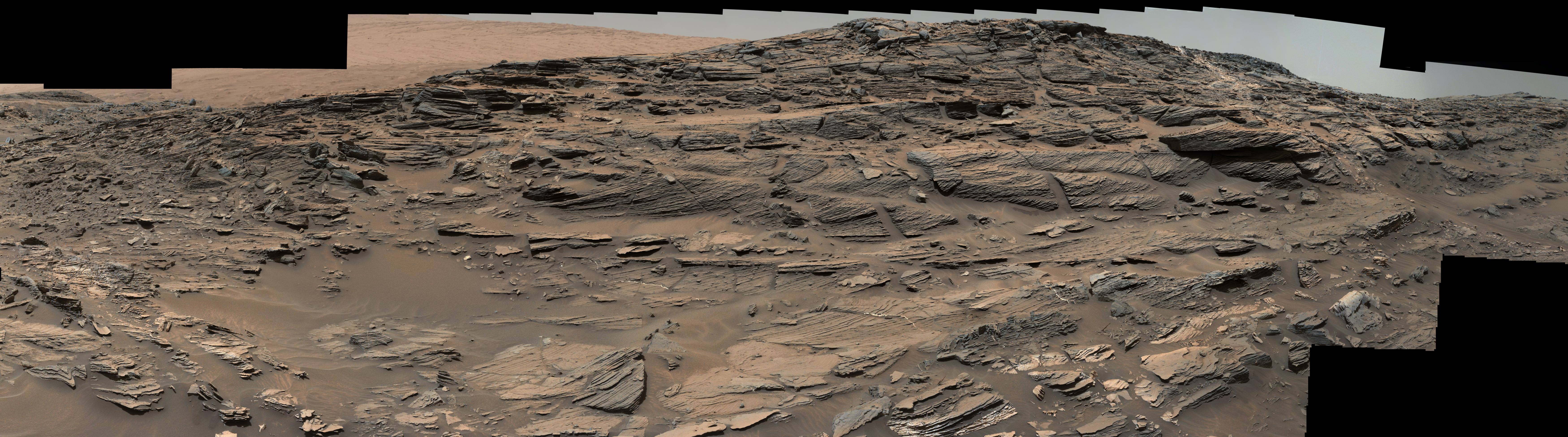 Large-scale crossbedding in the sandstone of this ridge on a lower slope of Mars' Mount Sharp is typical of windblown sand dunes that have petrified. NASA's Curiosity Mars rover used its Mastcam to capture this vista on Aug. 27, 2015. Similarly textured sandstone is common in the U.S. Southwest.  Credits: NASA/JPL-Caltech/MSSS