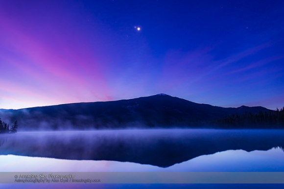 The conjunction of Venus (brightest), Jupiter (above Venus) and Mars (dimmer below Venus & Jupiter) looking east in the morning twilight on October 25, 2015, as seen from the west shore of Lake Annette, in Jasper National Park, Alberta. The mountain is the Watchtower. Morning mist covers the lake waters. Haze in the sky adds the natural glows around the planets — no filters were used.  Credit and copyright: Alan Dyer.