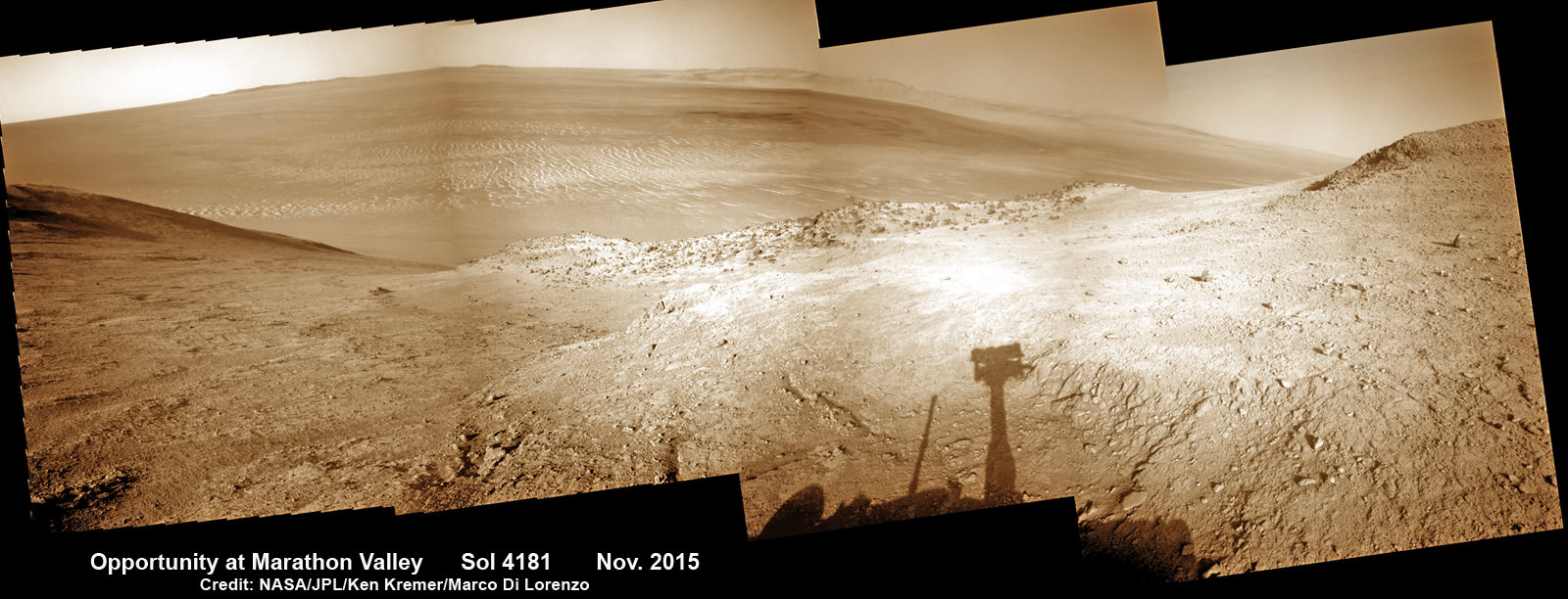 NASA's Opportunity rover peers outwards across to the vast expense of Endeavour Crater from current location descending along steep walled Marathon Valley in early November 2015. Marathon Valley holds significant deposits of water altered clay minerals holding clues to the planets watery past.  Shadow of Pancam Mast assembly and robots deck visible at right. This navcam camera photo mosaic was assembled from images taken on Sol 4181 (Oct. 29, 2015) and colorized. Credit: NASA/JPL/Cornell/Ken Kremer/kenkremer.com/Marco Di Lorenzo