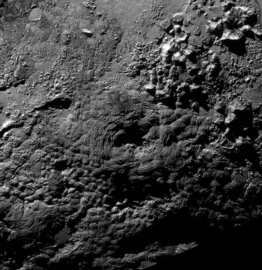 Ice Volcanoes on Pluto?  The informally named feature Wright Mons, located south of Sputnik Planum on Pluto, is an unusual feature that's about 100 miles (160 kilometers) wide and 13,000 feet (4 kilometers) high. It displays a summit depression (visible in the center of the image) that's approximately 35 miles (56 kilometers) across, with a distinctive hummocky texture on its sides. The rim of the summit depression also shows concentric fracturing. New Horizons scientists believe that this mountain and another, Piccard Mons, could have been formed by the 'cryovolcanic' eruption of ices from beneath Pluto's surface.   Credit: NASA/Johns Hopkins University Applied Physics Laboratory/Southwest Research Institute