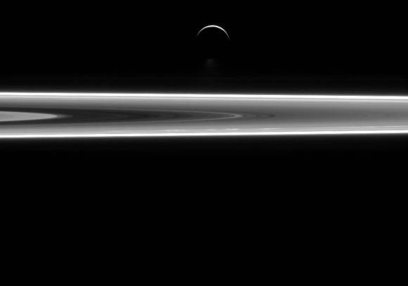 The crescent of Saturn's moon Enceladus hangs above the planet's rings in this image from the Cassini spacecraft. Water jets that spew from the moon's south pole region are also visible. Credit: NASA/JPL-Caltech/Space Science Institute