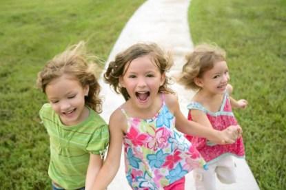 Tre bambine corrono sul prato felici.
