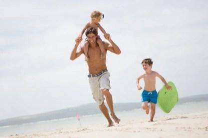 papà che corre sullaspiaggia con i figli