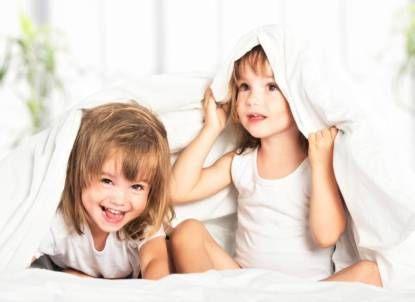 happy little girls twins sister in bed under blanket having